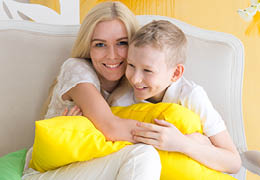 Happy mother hugging her adorable son while sitting on sofa